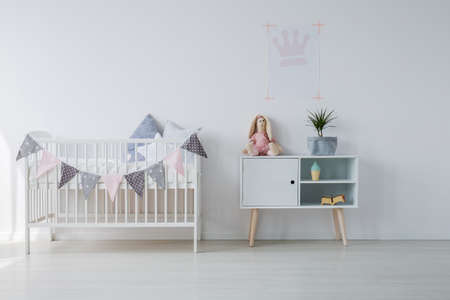 White wooden crib with pillows next to wooden cabinet with toy and green pant in grey, copy space on empty white wall Stock Photo