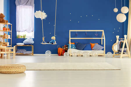 Blue wall with golden stars in chic scandinavian kid room with wooden bed with pillows and toys