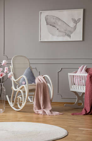 Blue pillow and paste pink blanket on white rocking chair in elegant baby room bedroom in tenement house