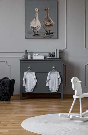 Little baby clothes hanging on grey wooden chest of drawers in elegant grey interior with wooden floor and molding on the wall Stock Photo