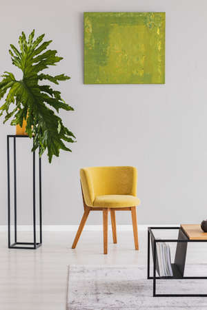 Plant next to yellow chair in modern living room interior with green poster on grey wall. Real photo