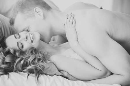 Happy woman embracing lover. Man kissing girlfriends neck during foreplay Stock Photo