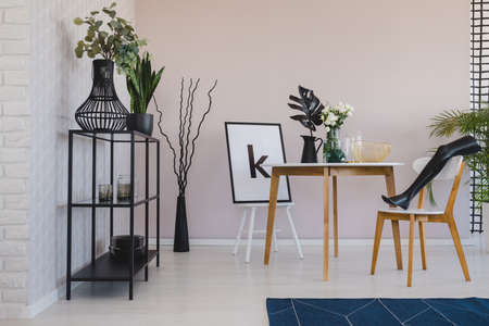 Black mannequins leg on wooden chair in elegant dining room interior with copy space on the empty wall, flowers and leaf in vases on the floor and poster on the chair
