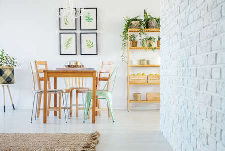 White brick wall in voguish dining room interior with wooden communal table and wooden and metal chairs, gallery of floral posters on the white empty wall