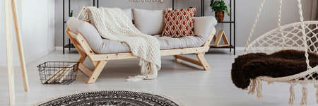 Light grey wooden sofa with knit blanket and patterned cushion in real photo of bright living room interior with hammock chair