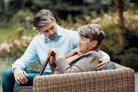Sad grey senior lady with walking cane sitting in the garden with her son 스톡 콘텐츠