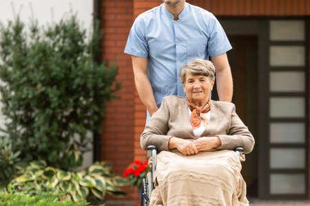 Senior pensioner on wheelchair in the garden of nursing home