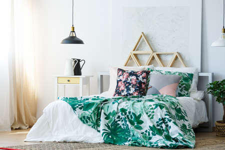 Floral bedding on double bed in stylish bedroom with painting and wooden triangles as headboard