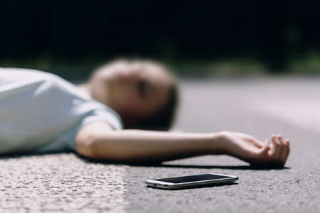 Close-up on a smartphone and careless victim of a traffic accident on a crosswalk