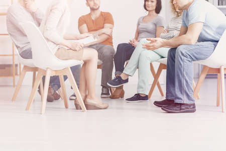 Close-up on people sitting in a circle during group therapy with counselor Banque d'images - 115272857