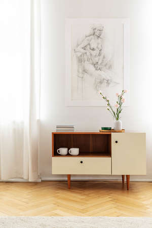 Poster on white wall above wooden cabinet with flowers in simple living room interior. Real photo