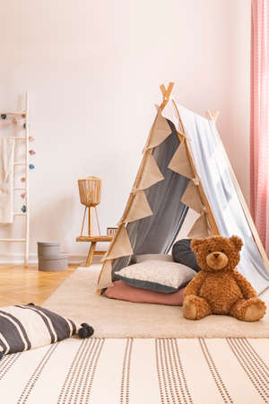 Plush toy in front of tent in childs room interior with carpet and patterned pillows. Real photo Reklamní fotografie
