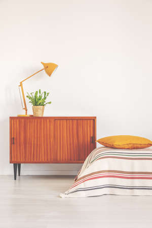 Yellow lamp and plant in pot on vintage cabinet in elegant bedroom interior, real photo with copy space on the empty wall Stock Photo