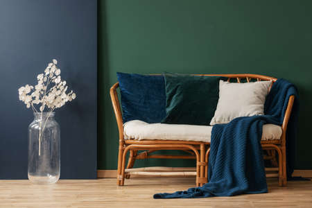 Blue blanket and pillows on rattan sofa next to white flowers in green apartment interior. Real photo