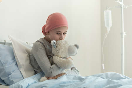Weak sick girl with headscarf hugging teddy bear next to drip in the medical center