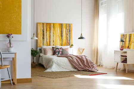 Almohada floral y sábanas de color rosa pastel en una cómoda cama en el interior del dormitorio contemporáneo con pintura elegante en la pared Foto de archivo