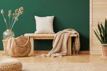 Decke und Kissen auf Holzbank im grünen Wohnungsinnenraum mit Hocker, Tasche und Pflanzen. Echtes Foto