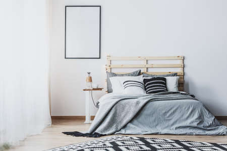 Mockup of empty poster in white bedroom interior with grey wooden bed with cushions. Real photo Banque d'images