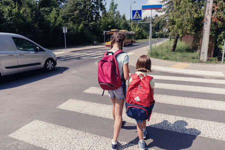 Children with backpacks walking to the school through a crosswalk next to a car