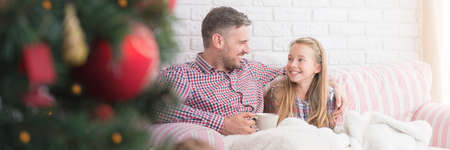 Talk between father and daughter sitting on sofa Stock Photo