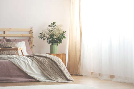 Beige blanket on wooden bed with tray in bright bedroom interior with flowers on table. Real photo Stockfoto