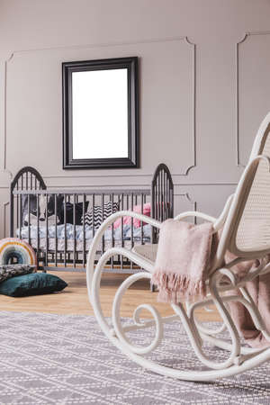 White rocking chair with pastel pink blanket in elegant little baby bedroom with grey wooden crib and mockup poster on the wall
