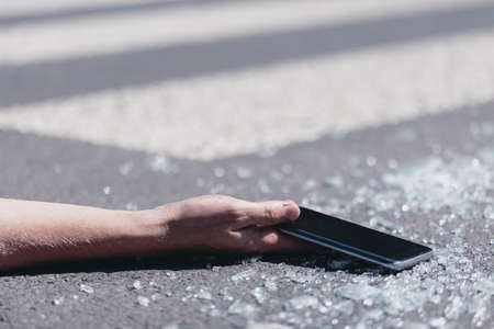 Close-up on a person with smartphone in a hand after accident on a pedestrian crossing Stock Photo - 115570350