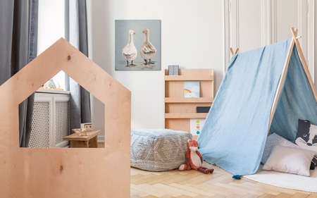 Wooden desk and blue tent with pillows in child's playground interior with pouf and poster. Real photo Archivio Fotografico