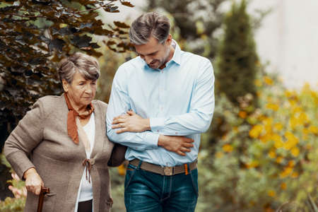 Worried grey senior lady with walking cane in the garden with her son