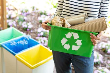 Close-up de una canasta verde con un símbolo de reciclaje con papeles sostenidos por una mujer Foto de archivo