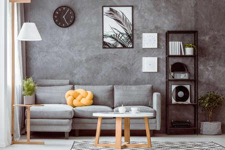 Szara betonowa ściana w nowoczesnym salonie z industrialną czarną metalową półką na książki obok wygodnej sofy z żółtą poduszką z węzłem