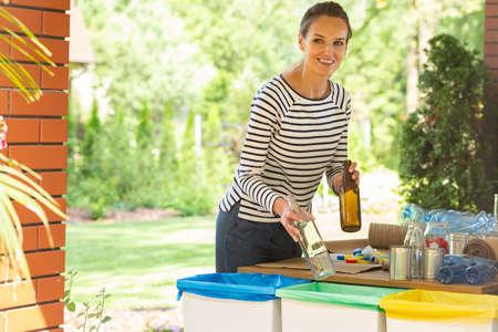 Woman segregating trash in her garden Stock Photo