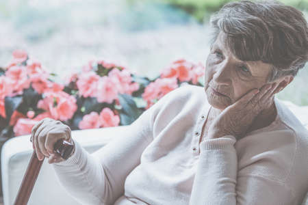 Sad old lady with cane sitting alone at home