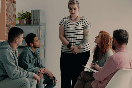 Sad teenage girl with tattoos talking about problems during meeting of support group