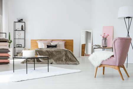 Chic bright bedroom with king size bed, industrial furniture and trendy pink armchair