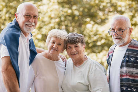 Group of senior friends smiling and having fun together at park