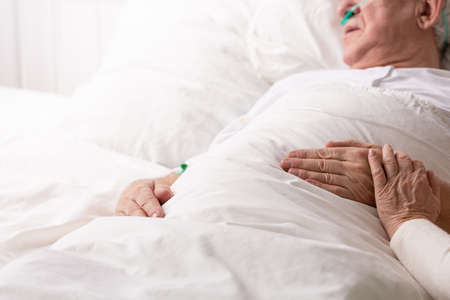 Senior man with terminal illness laying in hospital bed, helping and on his hand as symbol of support, photo with copy space