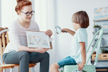 Smiling therapist showing picture of house to boy with magnifier during psychotherapy Stock Photo