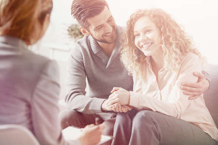 Bright photo of happy smiling married couple during therapy session with a psychologist Stock Photo