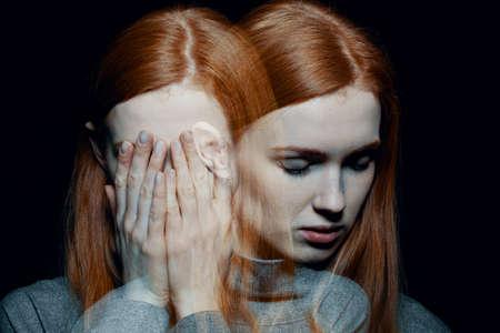 Porter de hermosa chica pelirroja con trastornos psicóticos que cubren su rostro, escondiéndose de sus alucinaciones, fondo negro detrás de ella