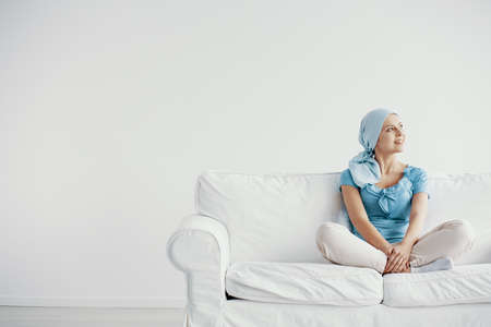 Pretty young woman suffering from cancer, wearing blue headscarf and siting cross leg on the couch at home before treatment, copy space on empty wall