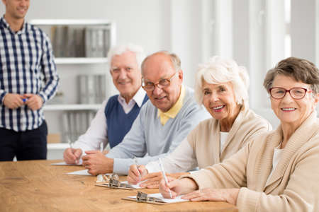 Happy group of elderly people with teacher before exam at third age university