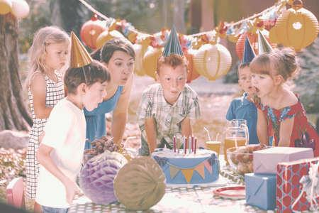 Niño pelirrojo y su madre soplando velas en el pastel de cumpleaños durante la fiesta en el jardín para niños Foto de archivo