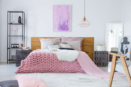 Satin beige pillows and fury white blanket on big comfortable bed in bright bedroom interior Stock Photo