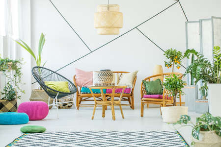 Trendy black armchair with pillow, urban jungle and patterned carpet in fashionable living room interior with rattan sofa, armchairs and coffee table Stock Photo