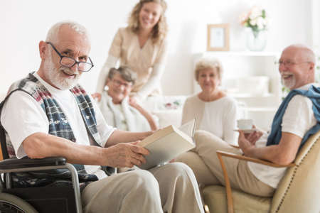 Old man with glasses sitting on wheelchair reading a book Stock Photo