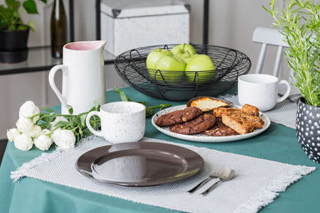 Stylish plateau with green apples next to plate with cookies, coffee mugs and plates on table