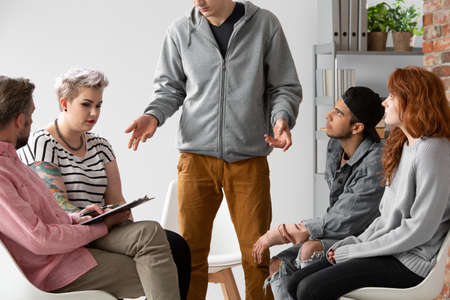 Man talking with young rebellious people with problems during therapy with psychologist