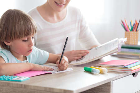 Boy with ADHD doing homework next to smiling mother with book