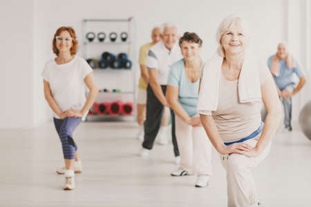 Smiling senior woman with towel exercising during yoga classes for elderly people Imagens